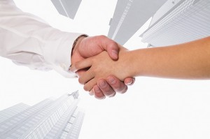 Business people shaking hands with skyscrapers in the background